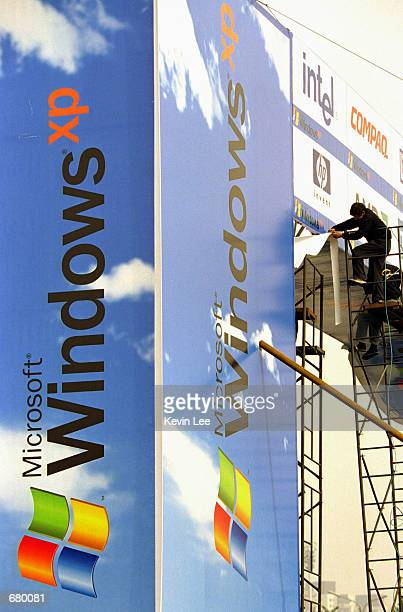 A worker puts the finishing touches on a Microsoft billboard featuring its latest software Windows XP at the entrance of a conference center November...