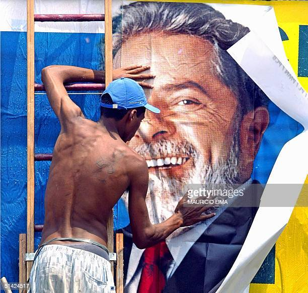A worker puts up a campaign sign for Brazilian presidential candidate Luiz Inacio Lula da Silva of theWorkers Party 24 October in Sao Paulo Brazil...