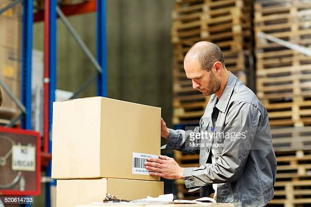 Worker putting barcode on box in warehouse