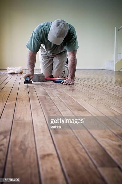 Worker putting finishing details on hardwood flooring
