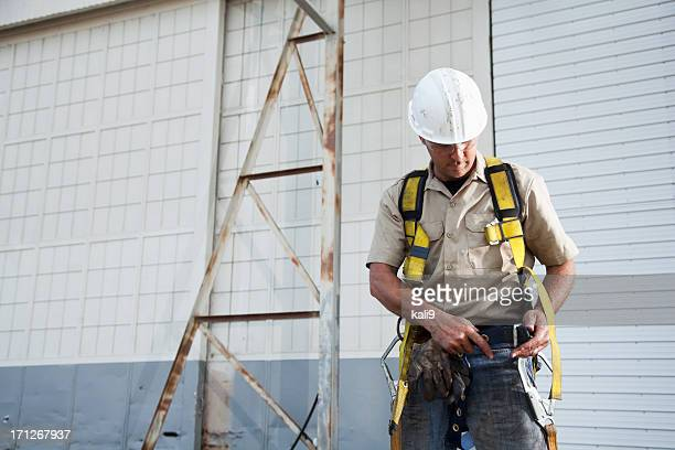 Worker putting on safety harness