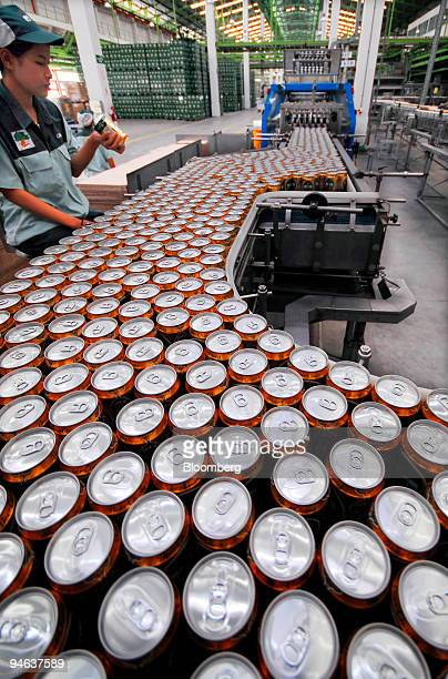 A worker quality checks beer cans on a conveyor belt at a Thai Beverage Plc Chang brewery in Kamphaeng Phet north of Bangkok on Monday May 22 2006...