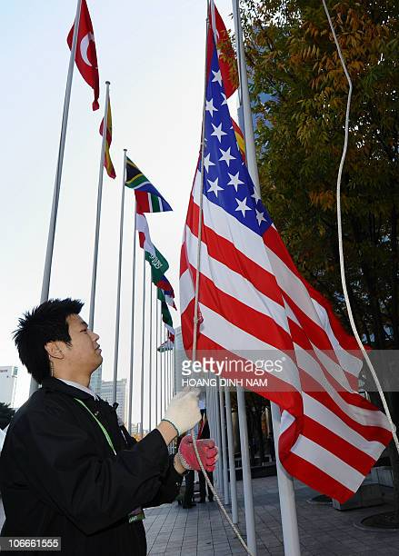 A worker raises the US flag alongside other flags of the participating G20 countries outside the venue of the G20 Summit in Seoul on November 10 2010...