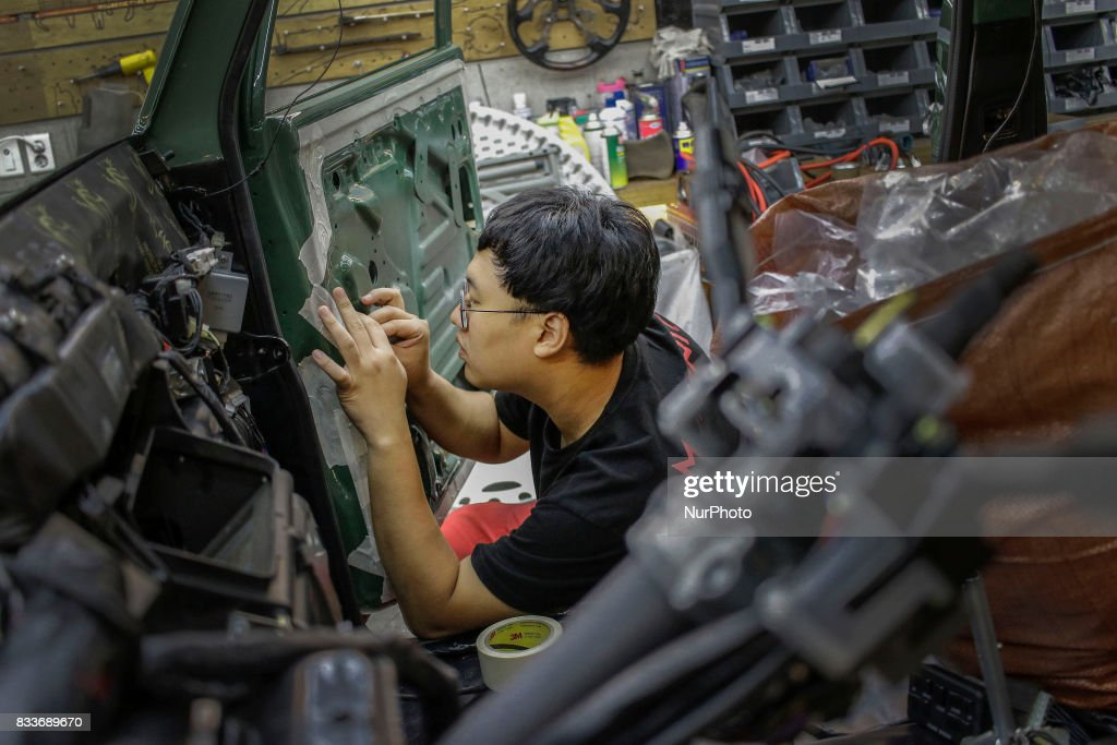 """Worker re install door interior at mohenic garage in Paju, South Korea. A 20-year-old beat up Hyundai SUV isn't anyone's idea of a dream car. But used Hyundai Gallopers, priced between $2,000 to $3,000 at second-hand car markets, are making a comeback , reborn as upwards $80,000 luxury vehicles at the hand of former furniture designer Henie Kim. Kim is now the CEO of Mohenic Garages, a car rebuilding company based in Paju has transformed the boxy classic into one of South Korea's most highly-desired cars. """"As a former designer, I wanted make everything perfect."""" The remade """"Mohenic G"""", as they're known, take their design cues from the 1990s and come in a variety of custom colors from """"mint racing green"""" to """"midnight cerulean blue"""". Demand for the """"Mohenic G"""" has steadily risen, and the waitlist is long. Since 2013, only 43 cars have been rebuilt and 48 customers are on a waiting list. Production is slow though since the company expanded, they're able to produce 30 cars a year, or about 2 cars a month. A team of two dozen workers transform each car in a meticulous process that includes prying the car cabin from its frame, sanding, removing corrosive substances, polishing and painting."""