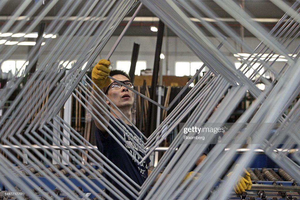 A Worker Reaches For A Frame To Assemble Glass For A Double Pane Window At