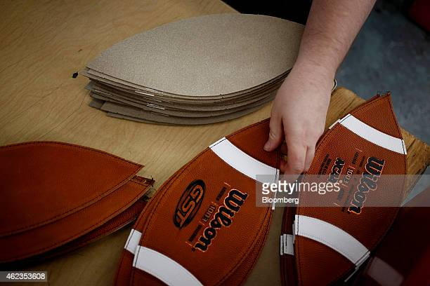 A worker reaches for a piece of leather to sew while manufacturing footballs at the Wilson Sporting Goods Co factory in Ada Ohio US on Monday Jan 26...