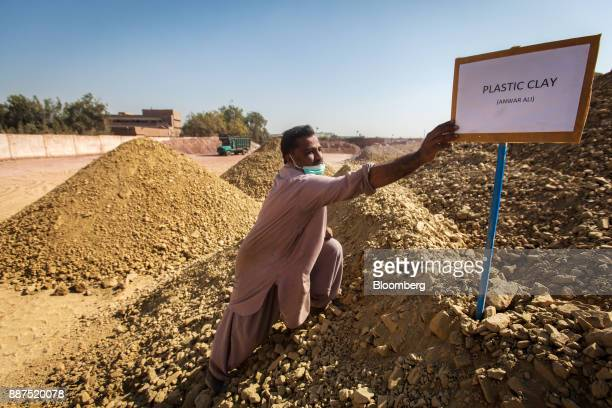 A worker reaches for a sign standing in a pile of clay in a preparation unit at the Shabbir Tiles Ceramics Ltd production facility in Karachi...