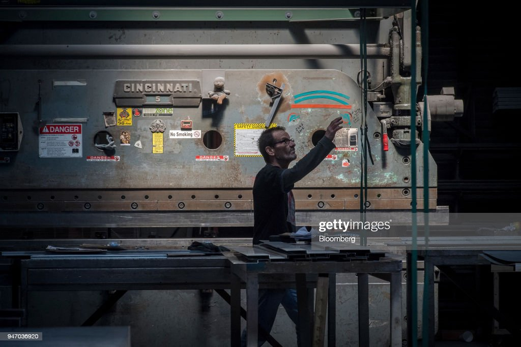 A worker reaches for a tie-down in front of a metal press brake at the Metal Manufacturing Co. facility in Sacramento, California, U.S., on Thursday, April 12, 2018. The Federal Reserve is scheduled to release industrial production figures on April 17. Photographer: David Paul Morris/Bloomberg via Getty Images