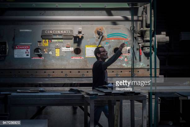 A worker reaches for a tiedown in front of a metal press brake at the Metal Manufacturing Co facility in Sacramento California US on Thursday April...