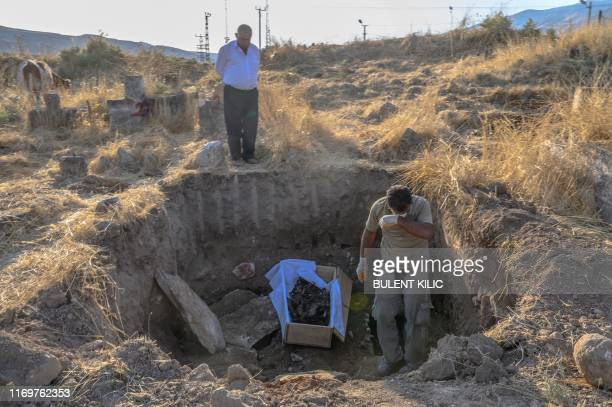 A worker reacts as he removes a corpse as a relative watches him at the Hasankeyf cemetery in Hasankeyf at on the banks of the Tigris in southeastern...
