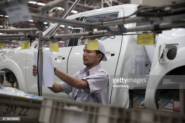 A worker reads a document while standing near the body of a Nissan Motor Co Navara pickup truck on an assembly line at the company's plant in Samut...