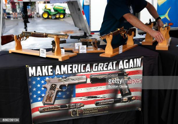 A worker rearranges the guns inside the booth at Commemorative Firearms as fans stopped by to check out guns bearing Trump's motto 'Make America...