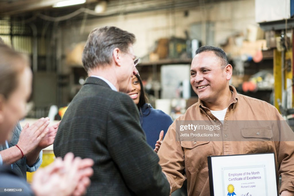 Worker receiving award in workshop : Stock Photo