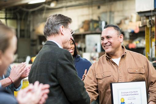 Worker receiving award in workshop - gettyimageskorea