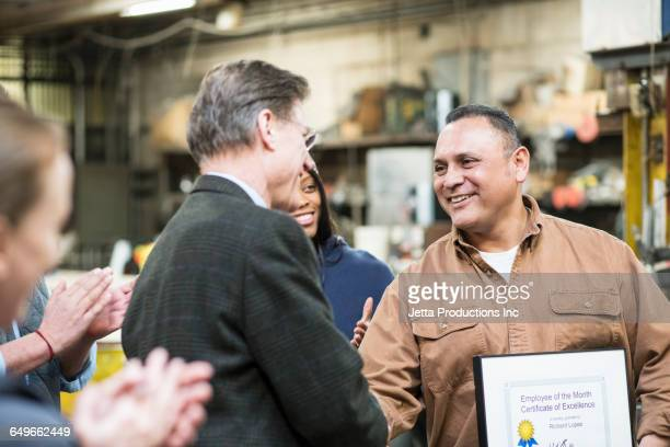 worker receiving award in workshop - award stock pictures, royalty-free photos & images