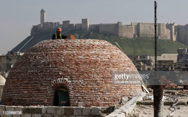 Worker reconstructs a dome on the rooftop of Aleppo's covered market 'Souk al-Saqatiyeh' in front of the northern Syrian city's citadel on February...