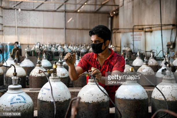 Worker refills oxygen cylinders inside an oxygen factory amid a countrywide lockdown due to the coronavirus in Dhaka. Demand for oxygen is increasing...