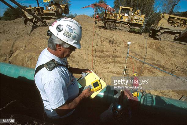 A worker registers the GPS coordinates on a piece of pipeline before it is buried in a 15foot trench October 3 2000 in Howell Michigan 60 miles north...