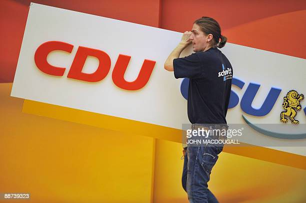 A worker removes a CDU and CSU logo after a special congress of the Christian Democratic Union and the Christian Social Union to put forth their...