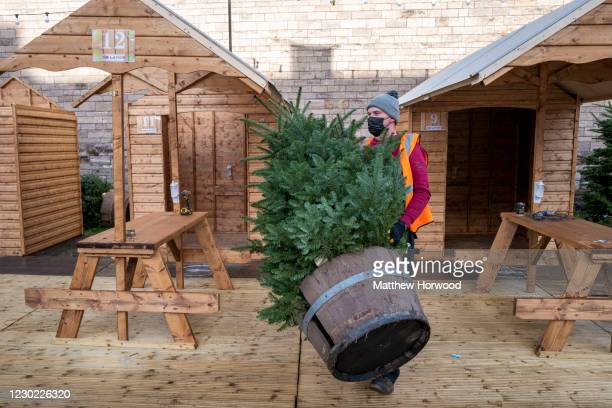 Worker removes a Christmas tree from Cardiff Castle on December 20, 2020 in Cardiff, Wales. All non-essential shops will close as of midnight, and...