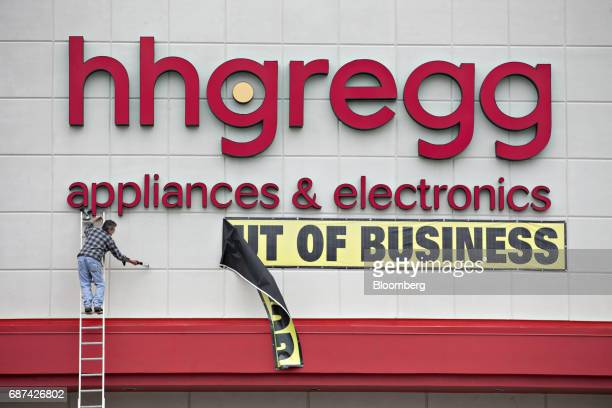 A worker removes a Going Out Of Business banner outside a HHGregg Inc store in Downers Grove Illinois US on Tuesday May 23 2017 The bankrupt retailer...