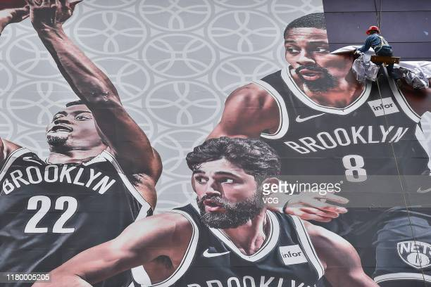 A worker removes a large poster from a building ahead of NBA Shanghai Game 2019 between Brooklyn Nets and Los Angeles Lakers at the Lujiazui Zhengda...