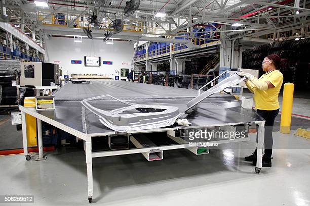 A worker removes a part as it comes out of a new $63 million press at the Fiat Chrysler Automobiles US Warren Stamping Plant January 22 2016 in...