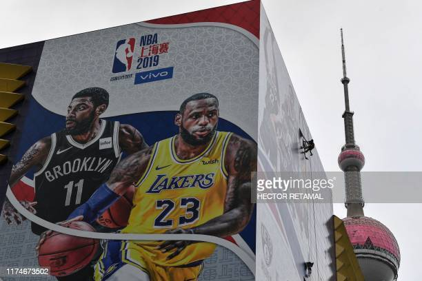 A worker removes a promotional banner from a building for the National Basketball Association October 10 preseason game in China between the Brooklyn...