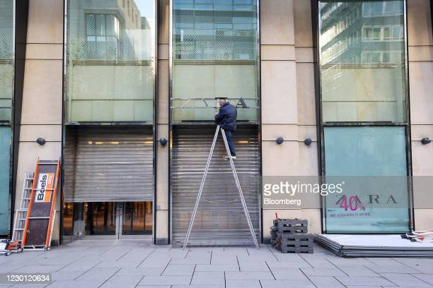 Worker removes a sign outside a closed Zara clothing store, operated by Inditex SA, in Frankfurt, Germany, on Monday, Dec. 14, 2020. Germany will...