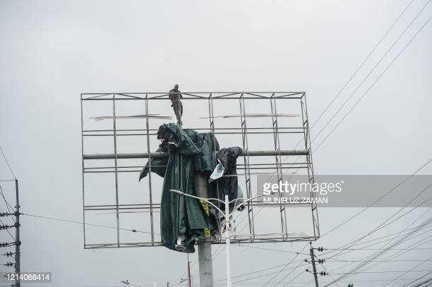 A worker removes a tarpaulin from an advertising structure ahead of the expected landfall of cyclone Amphan in Khulna on May 20 2020 India and...