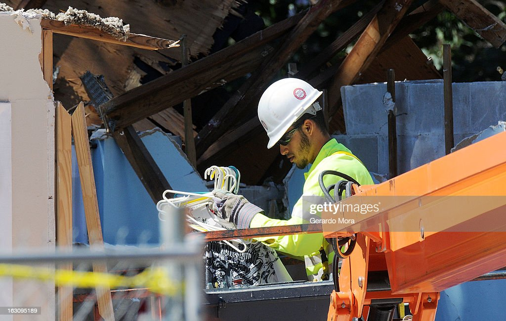 A worker removes belongings from the home where a sinkhole swallowed Jeffrey Bush on March 4, 2013 in Seffner, Florida. Jeff Bush, presumed dead after a sinkhole, estimated at 60 feet deep, opened under his bedroom while he was sleeping in the home. Demolition crews are working to raze the house, recover possessions, and stabilize the now-shaky ground.