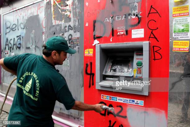 A worker removes graffitis on a destroyed cash machine at Istanbul Taksim square on June 12 2013 after a large cleanup operation removed all evidence...