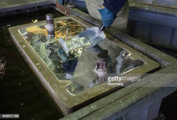 A worker removes impurities from a cooling zinc ingot in the rotary foundry room at the Chelyabinsk Zinc Plant operated by Ural Mining and...