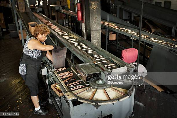 A worker removes pencils from a conveyor belt at the General Pencil Co's factory in Jersey City New Jersey US on Wednesday June 22 2011 General...