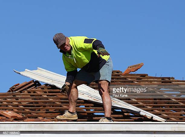 A worker removes roof tiles from a storm damaged house in Clarke Street on July 15 2014 in Hilton Australia Clean up commences after wild weather...