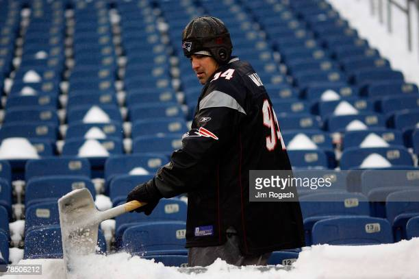 A worker removes snow from the stands befor a game between the New England Patriots and the New York Jets at Gillette Stadium on December 16 2007 in...