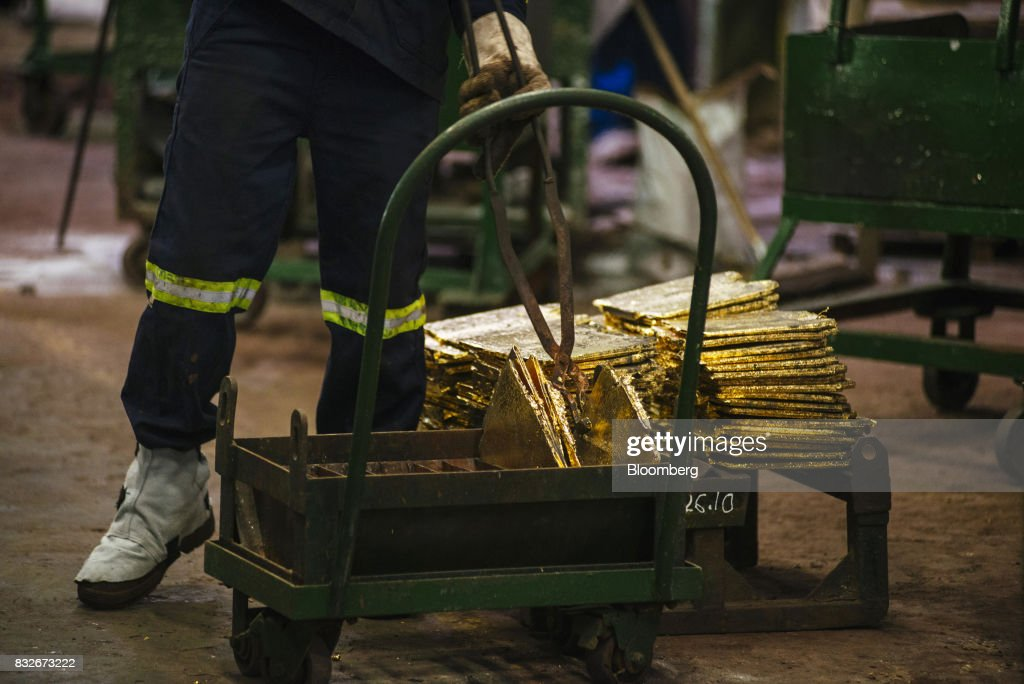 A worker removes solid gold slabs from a tray following the electro refining process to remove impurities at the Rand Refinery Ltd. plant in Germiston, South Africa, on Wednesday, Aug. 16. 2017. Established by the Chamber of Mines of South Africa in 1920, Rand Refinery is the largest integrated single-site precious metals refining and smelting complex in the world, according to their website. Photographer: Waldo Swiegers/Bloomberg via Getty Images