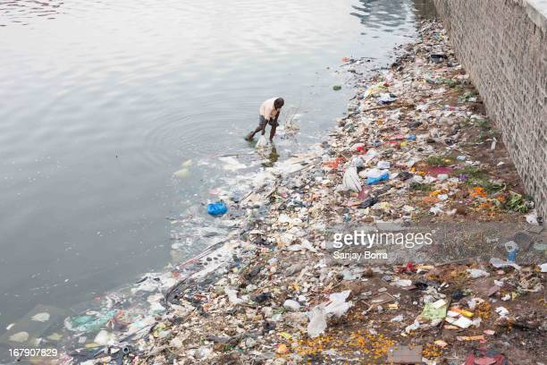 CONTENT] A worker removes the plastic covers and other wastage from the banks of Hussain Sagar lake
