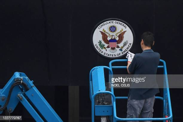 Worker removes the sign at the entrance to the US consulate in Chengdu, in Sichuan province on July 25, 2020. - China on July 24 ordered the US...