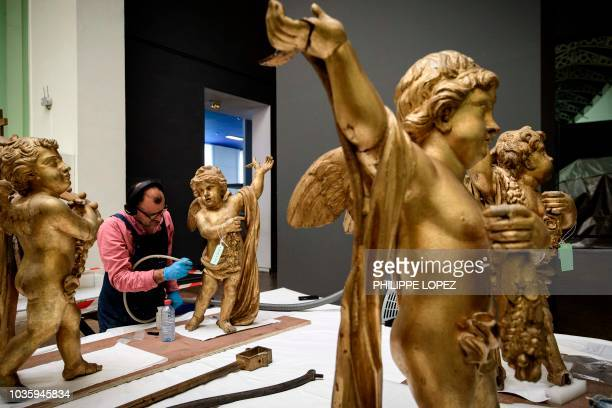 A worker renovates decoration statues on September 19 2018 which are part of the France's Imperial Canoe of Napoleon I before being transferred along...