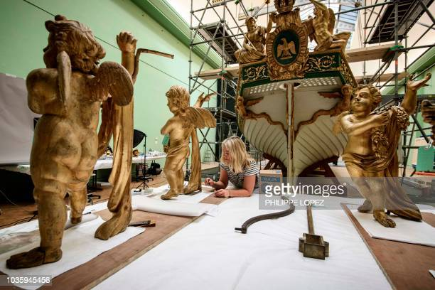 A worker renovates decoration statues on September 19 2018 which makes up part of France's Imperial Canoe of Napoleon I before being transferred...