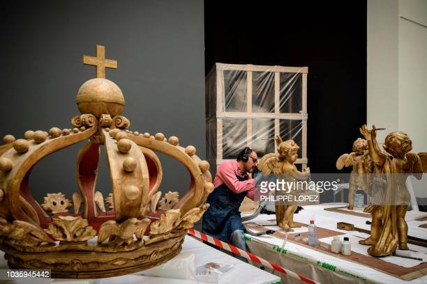A worker renovates on September 19 2018 decoration statues next to the crown which are part of the France's Imperial Canoe of Napoleon I a day after...