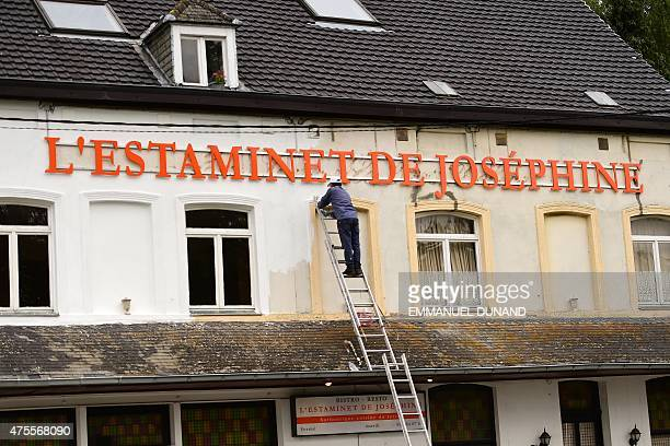 A worker repaints a restaurant to the name of Napoleon's wife Josephine near La Butte du Lion the main memorial monument of the Battle of Waterloo...