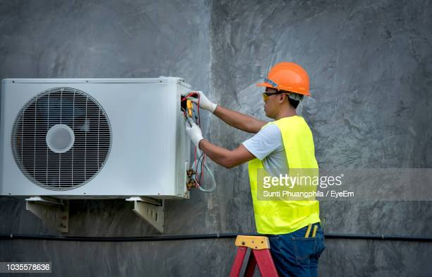 worker repairing air conditioner - air conditioning stock pictures, royalty-free photos & images