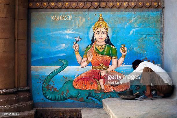Worker repairing the ghats by a wall painting of the Goddess Ganga the Ganges river's Hindu deity Varanasi Uttar Pradesh India