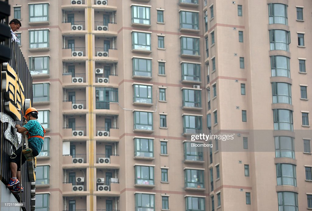 A worker repairs a sign above a restaurant, left, in front of a residential building in Shanghai, China, on Sunday, June 30, 2013. China's President Xi Jinping said officials shouldn't be judged solely on their record in boosting gross domestic product, the latest signal that policy makers are prepared to tolerate slower economic expansion. Photographer: Tomohiro Ohsumi/Bloomberg via Getty Images