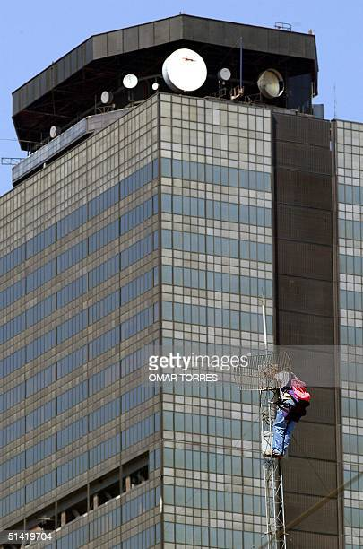 A worker repairs an antena on a building infront of the PEMEX building in the capital of Mexico 22 January 2002 Un operario repara una antena en un...