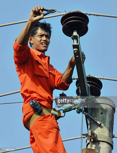 A worker repairs wiring of an electric post in Pangandaran 19 July 2006 after a earthquaketriggered tsunami hit south coast of Java island 17 July...