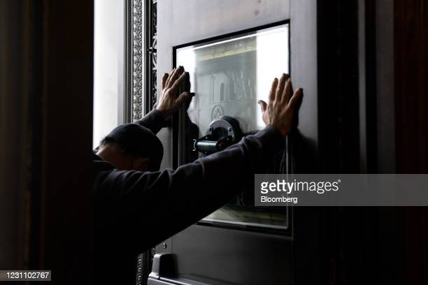Worker replaces a window that had been broken in the January 6 riots at the U.S. Capitol in Washington, D.C., U.S., on Thursday, Feb. 11, 2021. House...