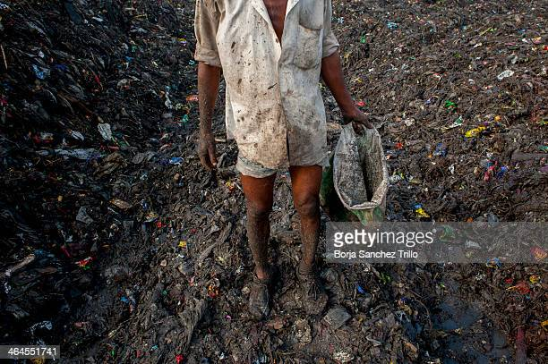 A worker rest a few seconds before restart to picking through trash in a landfill on November 17 2013 in Dhaka Bangladesh Bangladesh currently holds...